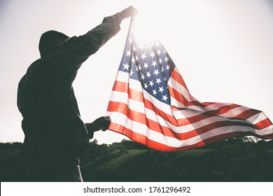 An American soldier with the US flag in his hands looks into the distance.