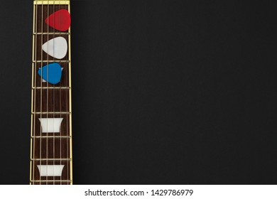 American style electric guitar neck with red, white and blue picks. The colors make the picture patriotic for the 4th of July. The neck is rosewood with white inlays. Includes copyspace. Dark