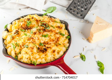 American style macaroni pasta with cheesy sauce and crunchy breadcrumbs topping, in portioned pan, white marble table, copy space