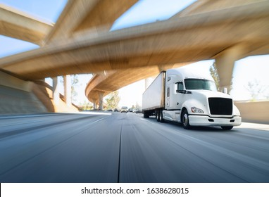 American style truck on freeway pulling load. Transportation theme. Road cars theme. Truckers heaven. Trailer passing the bridge
