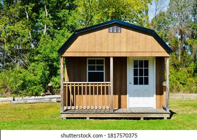 American style wooded shed, with porch. A shed is typically simple, single-story roofed structure in a back garden or on an allotment that is used for storage, hobbies, or as a workshop. Exterior view