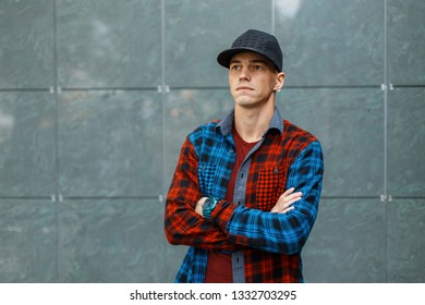 American stylish attractive young man in a fashionable t-shirt in a stylish blue and red plaid shirt in a black trendy basketball cap poses near a gray vintage wall. Cool fashion guy.
