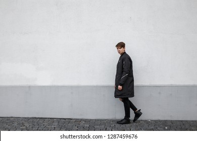 American stylish young man hipster in a long light jacket in trendy black jeans with a hairstyle in trendy sneakers walking along the street near the vintage wall. Fashionable modern guy.