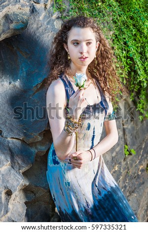 914c00aafcc American teenager girl with curly hair, wearing patterned dress, bracelet,  standing against rocky