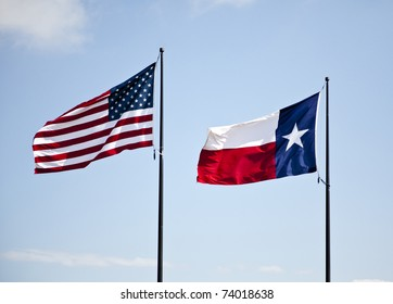 The American and Texas flags flying high together against a blue lightly cloudy sky.