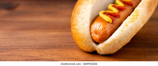 American traditional fast food Hotdog with fresh organic bread bun white wheat and black charcoal sausage ketchup mustard for meal with roasted onion pickle and French fries wedges and coleslaw