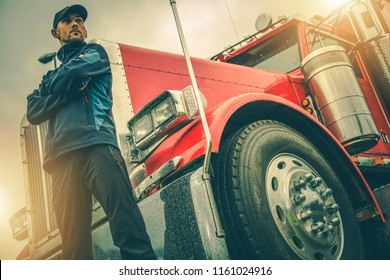 American Trucker Job. Caucasian Truck Driver in Front of His Red Semi Truck.