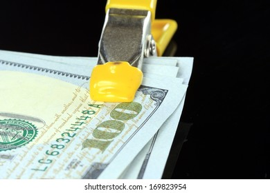 American US one hundred dollar bills money squeezed tight in a clamp isolated on black background