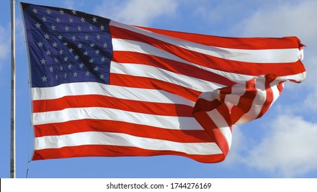 American USA flag on a flagpole waving in the wind. Close up of American flag waving.