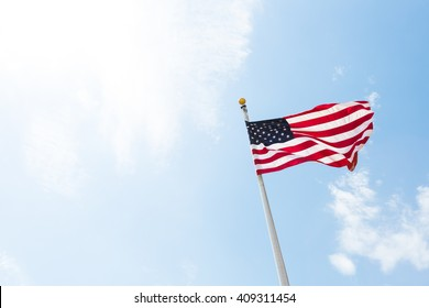 American USA flag :red, white and blue, stars and stripes) blowing in the wind on a flagpole against blue bright sunny skies
