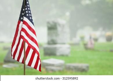 American veteran flag in a foggy cemetery. Vertical format.
