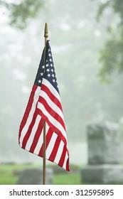 American veteran flag in a foggy cemetery. Vertical format. - Shutterstock ID 312595895