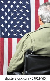American veteran in wheelchair and fatigues facing flag