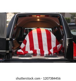 American veteran's flag draped casket in a hearse, ready for transport to his final resting place.