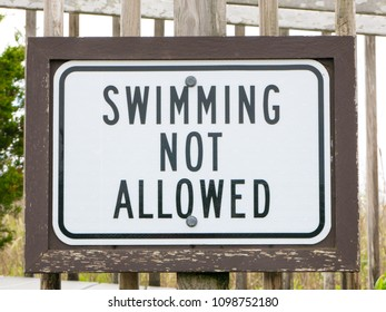 An american warning sign at the beach with man swim and not symbol, Caution No Swimming allowed
