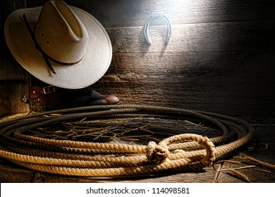American West authentic rodeo cowboy lariat lasso with end loop rawhide speed burner on aged barnwood floor with straw hat atop western boots in an old wooden ranch barn in soft and diffused sunlight
