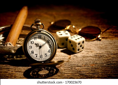 American West legend antique pocket watch with gambler craps dice and cigar in an old ashtray waiting on a vintage western saloon wood table ready for gambling and cheating at a game