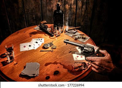 American West Legend armed gambler bandit holding revolver gun in hand and threatening cheater cowboy after poker cards game incident with cheating and drinking in an old western gambling saloon scene