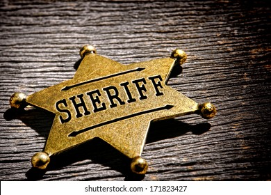 American West Legend law enforcement officer antique sheriff deputy star shape gold color brass badge as vintage western lawman identification and prestige shield on old frontier jail office table