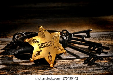 American West Legend law enforcement officer lawman sheriff deputy brass star badge on old vintage western handcuffs with antique jail keys on a frontier prison jailer office weathered wood table