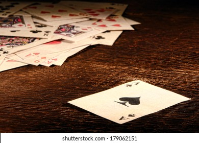American West Legend vintage ace of spade playing card and stack of antique poker game cards on a weathered wood table in an old western frontier gambling establishment saloon