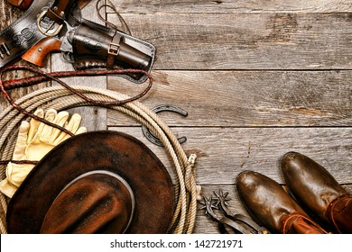 American West legend western cowboy ranching gear still life with old revolver gun in leather holster along lariat lasso and antique hat near boots and spurs on wood board ranch barn floor background