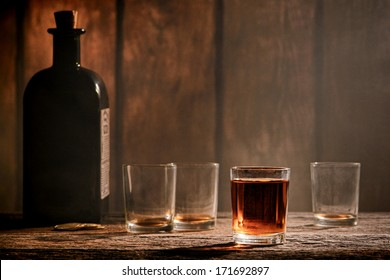 American West legend whiskey shot glass whisky drink and empty dirty alcohol glasses with antique whiskey bottle on an antique wood bar counter in a vintage Western saloon