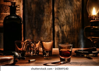 American West legend whisky shot glass drink with empty glasses and vintage whiskey bottle on antique wood bar counter with cowboy revolver gun in an antique frontier saloon scene lit by dim oil lamp
