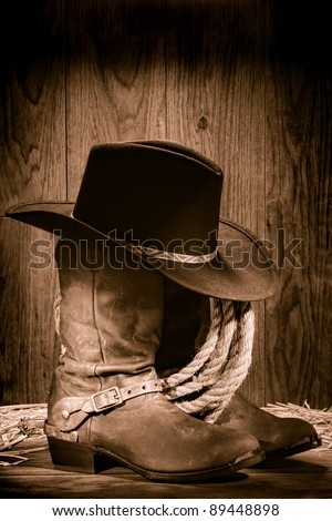 60480a1b75f04 American West rodeo cowboy black felt hat atop worn western boots and spurs  with old ranching