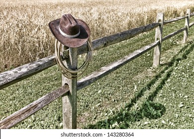 American West rodeo cowboy brown hat and roping lasso lariat hanging on an old wood fence post on a western ranch field
