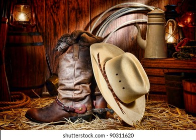American West rodeo cowboy traditional white straw hat on leather rancher roper boots with authentic Western riding spurs in vintage ranch barn with antique ranching supplies lit by kerosene lantern