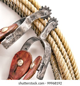 American West rodeo cowboy western riding spurs with worn rowel on authentic ranching lariat lasso over white