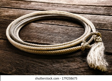 American West rodeo genuine cowboy lariat lasso with honda noose loop over rawhide speed burner and end tassel on vintage weathered barn wood planks in a western ranch