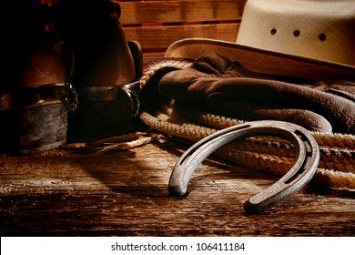 American West rodeo old horseshoe on lariat lasso and roping work gloves with Western horse rider gear with hat and aged leather roper boots on antique wood boars in a ranch barn