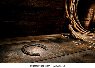 American West rodeo rusty old forgotten western horseshoe on ranch barn wood floor with lasso lariat on antique wooden wall