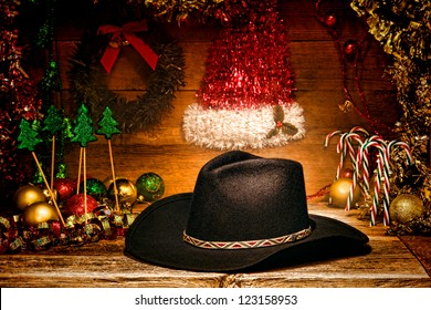 American West rodeo traditional black felt cowboy hat on wood vintage shelf with festive Christmas display decoration in authentic country and western motif for a nostalgic Christmastime greeting card