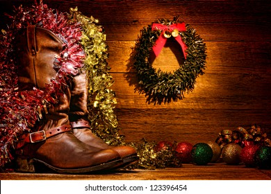 American West rodeo traditional leather cowboy boots in vintage wood cabin with festive merry Christmas display decoration in authentic country western decor for nostalgic Christmastime greeting card