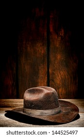 American west rodeo used and worn brown felt hat with dirty band on old wood plank in a weathered wooden barn