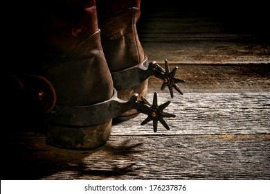 American West rodeo vintage Western riding spurs on traditional leather cowboy boots with dirty worn heels on old weathered wood planks in a western ranch