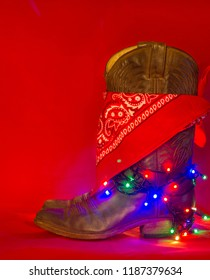 American West traditional boots and cowboy bandanna on christmas red background for text