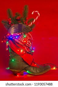 American West traditional cowboy boot and bandanna on christmas red background for text