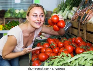 american woman customer picking fresh ripe tomatoes in food store