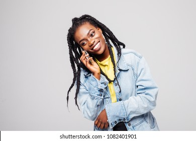American woman smiling and speaking on black mobile phone isolated over gray background