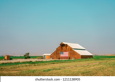 American wooden farm with the flag of United States in the front and white roof. Beautiful green farmland.