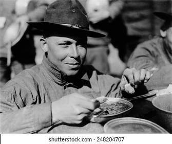 American WW1 soldier eating from his mess kit. 1917-18.