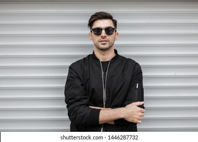American young brunette man with a stylish hairstyle in dark sunglasses in a fashionable black jacket stands near a white metallic wall in the city. Attractive modern hipster guy. Trendy menswear.