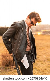 American young man model in stylish sunglasses in fashion leather black jacket in shirt relaxes on bright sun outdoors in the evening. Sexy hipster guy enjoys orange sunlight at sunset. Casual style.
