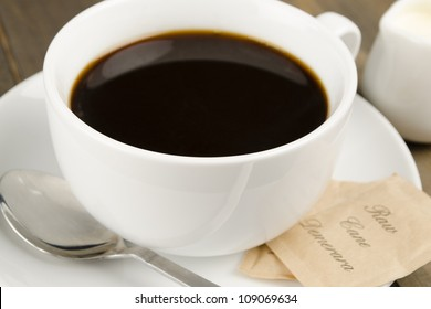 Americano black coffee in a white cup with raw demerara sugar sachets and a jug of milk.
