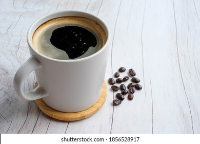 americano with Coffee beans on wood texture background