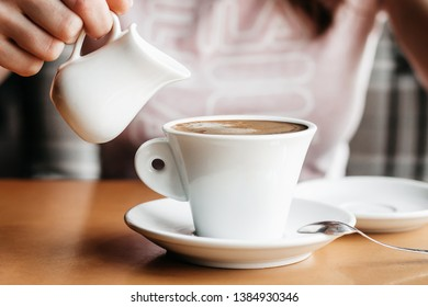 Americano coffee. Girl pours milk into a cup of americano coffee. Coffee with a milk